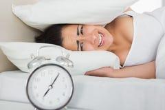 Oídos de la cubierta de la mujer con las almohadas en cama Fotografía de archivo libre de regalías