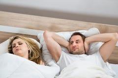 Oídos de la cubierta del hombre mientras que el dormir de la mujer Fotografía de archivo