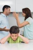 Oídos de la cubierta del muchacho mientras que padres que pelean en cocina Foto de archivo libre de regalías