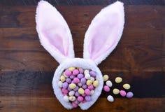 Oídos del conejito de pascua con los huevos de caramelo Imagenes de archivo