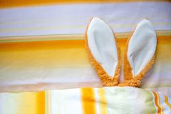 Oídos del conejito de pascua en cama debajo de bedsheets fotos de archivo