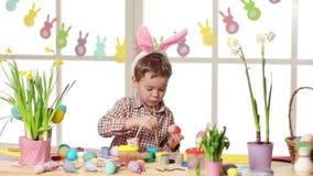 Oídos del conejito del niño que llevan feliz que pintan los huevos el día de Pascua almacen de metraje de vídeo