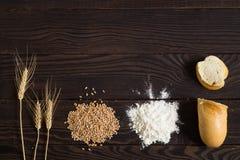 Oídos del trigo, granos, harina y pan cortado en una tabla de madera oscura Fotos de archivo