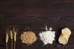 Oídos del trigo, granos, harina y pan cortado en una tabla de madera oscura Foto de archivo