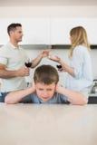 Oídos irritados de la cubierta del muchacho mientras que discusión de los padres Fotos de archivo libres de regalías