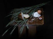 Oídos, pan, huevo, harina, cáscara de huevo en la tabla de madera Backgro negro Imagenes de archivo