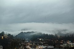 Облака над передавая башней на верхней части холма Туманная погода после дождя заволакивает драматическое света города стоковые изображения