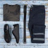 Обмундирования ` s людей вскользь Ботинки, одежда и аксессуары людей на деревянной предпосылке - футболке, джинсах, тапке, поясе  стоковые изображения