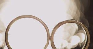 Обручальные кольца лежа на темной поверхности светя со светлым концом вверх по макросу Отражение Черная предпосылка видеоматериал