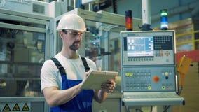 Оборудование бензина и мужской техник работая рядом с ним акции видеоматериалы