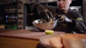 Овощи взрослого шеф-повара смешивая в большом алюминиевом шаре с рукой на предпосылке Плита с частью рыб на переднем плане видеоматериал