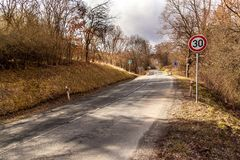 Ограничение в скорости дорожного знака на дороге в чехии Опасное место на дороге Дорога асфальта в сельской местности стоковое изображение rf