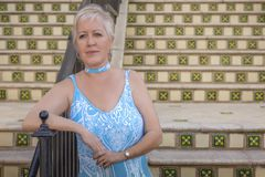Ожидания зрелые современные белокурые женщины на дне шагов полагаясь на рельсе стоковое фото