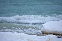Океанские волны с валунами льда на береге стоковое фото