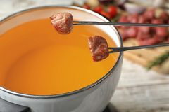Окунать мясо в бак фондю с маслом на таблице стоковые фотографии rf