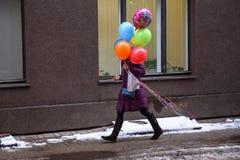 Оман идя на улицу с красочными воздушными шарами на руках стоковые изображения rf