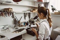 Она знает чего она делает Портрет женского ювелира смотря новый продукт украшений через микроскоп в a стоковые фото