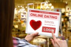 Онлайн концепция датировка, девушка держит цифровую таблетку на запачканной предпосылке магазина стоковое изображение rf