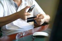 Онлайн-платеж: Человек держа умные телефон и кредитную карточку готовыми сделать приобретение стоковое фото