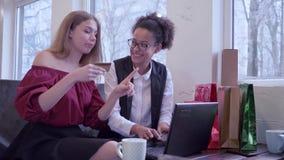 Онлайн приобретение, счастливые международные девушки использует ноутбук электронных денег и компьютера для приобретений интернет акции видеоматериалы
