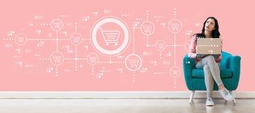 Онлайн тема покупок при женщина используя компьтер-книжку стоковое фото