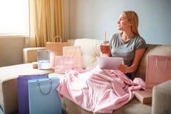 Он-лайн покупка дома Молодая белокурая женщина с чаем ждет ее заказ от онлайн магазина пока сидящ с стоковая фотография rf