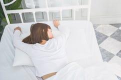 Он носит белое платье для того чтобы спать стоковая фотография rf
