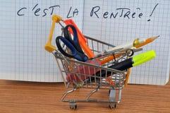 Оно назад в школу написанную во французском с caddy заполненным со школьными принадлежностями бесплатная иллюстрация
