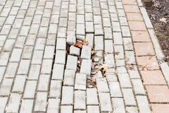 Опасное отверстие для пешеходов на поврежденном тротуаре со сломленными кирпичами на городской улице города стоковая фотография rf