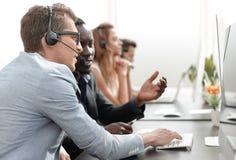 Операторы центра телефонного обслуживания говорить, сидя на его столе стоковое изображение