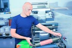 Оператор принтера рядом с печатной машиной, держа печать цилиндра с плитой сброса полимера вставленной на ей стоковое фото rf
