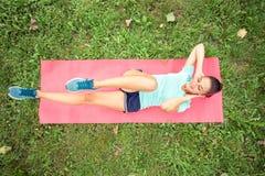 Определенный подходящий делать молодой женщины сидеть-поднимает в парке стоковая фотография rf