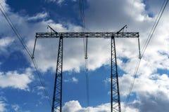 Опоры высоковольтных линий электропередач и голубое небо с облаками стоковое фото