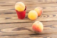Один свежий весь зрелый персик в красном ведре металла и 3 персиках отдельно стоковое фото rf