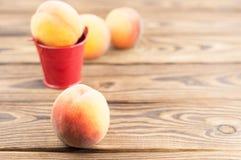Один свежий весь зрелый персик в красном ведре металла и 3 персиках отдельно стоковые фотографии rf