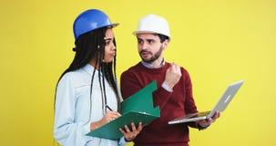 Один специалист в конструкции и молодой африканский инженер дамы имеют обсуждение о плане здания перед акции видеоматериалы