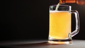 Освежая пиво лить от бутылки в стеклянный вращать кружки изолированный на черной предпосылке сток-видео