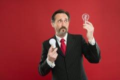Освещать выборы для сохранения денег Электрическая лампочка владением костюма бородатого консультанта человека официальная на кра стоковое фото