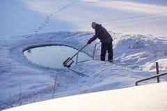 Отверстие льда в озере в зиме оборудовано с лестницей для запускать Человек очищает отверстие льда стоковые изображения rf