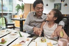 Отец имеет обедающий с его дочерью стоковое фото