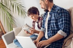 Отец и меньший сын дома сидя на папе софы работая на ноутбуке смотря видео мальчика наблюдая на цифровом планшете стоковое изображение rf