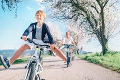 Отец и сын имея потеху распространяя широкие ноги и кричащее ехать велосипеды на проселочной дороге под деревьями цветения Здоров стоковое фото