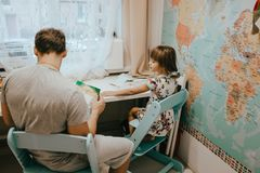 Отец помогает его маленькой дочери сделать уроки на столе в комнате с картой на стене стоковое фото rf