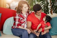 Отец разговаривая с маленькой семьей промежутка времени дочери имея остатки на софе стоковая фотография