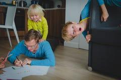 Отец остается домом с сыном и дочь, дети имеет потеху стоковые изображения rf