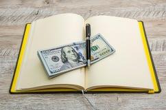 Открытые тетрадь, ручка и доллары на деревянном столе стоковая фотография rf