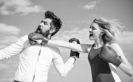 Отношения как концепция схватки Человек и женщина воюют предпосылку голубого неба перчаток бокса Защитите ваше мнение внутри стоковые фотографии rf
