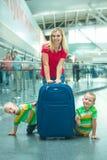 Отдых в аэропорте Семья ждет свой полет 2 брать играют, прячущ за большим чемоданом стоковые фотографии rf