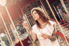Отдых Ourdoors Девушка в положении шляпы на парке атракционов с усмехаться пузырей бутылки дуя счастливый стоковые фотографии rf