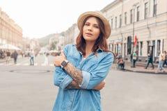 Отдых Ourdoors Девушка в шляпе идя на улицу города пересекла оружия уверенные стоковое изображение rf